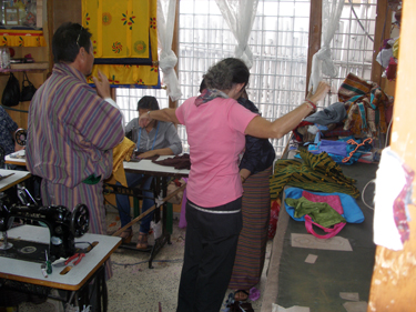Sheila being measure in tailor's shop