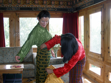 Sheila being dressed by girl at hotel